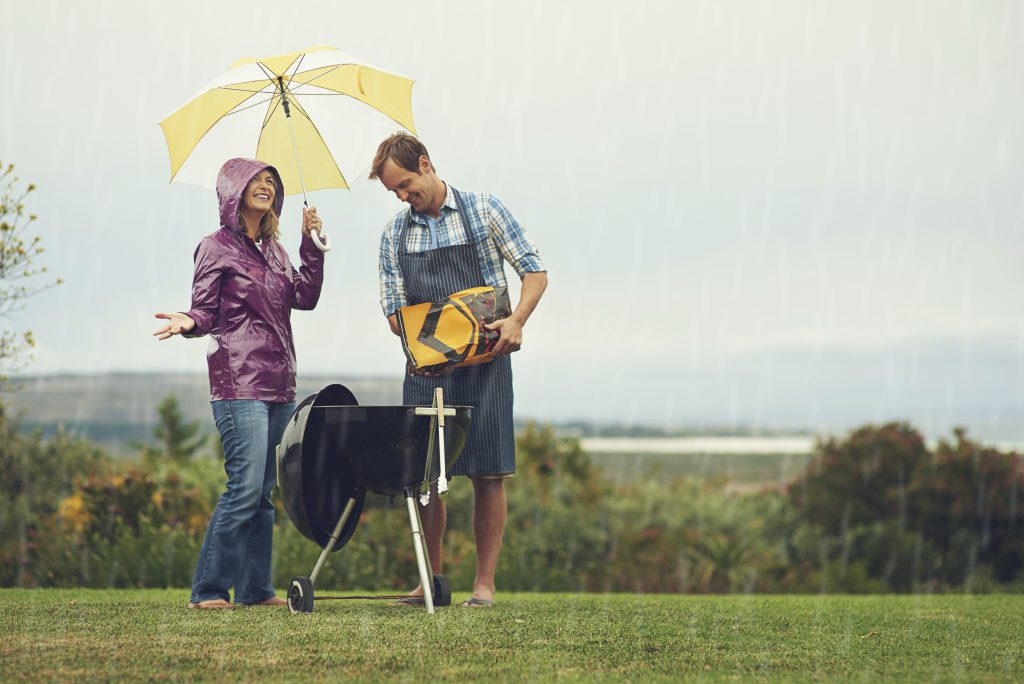 Shot of a couple happily  barbecuing in the rainhttp://195.154.178.81/DATA/i_collage/pi/shoots/805776.jpg
