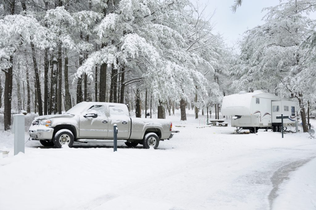 RV travel trailer fifth wheel and pickup truck parked in snowy campground with copy space below.