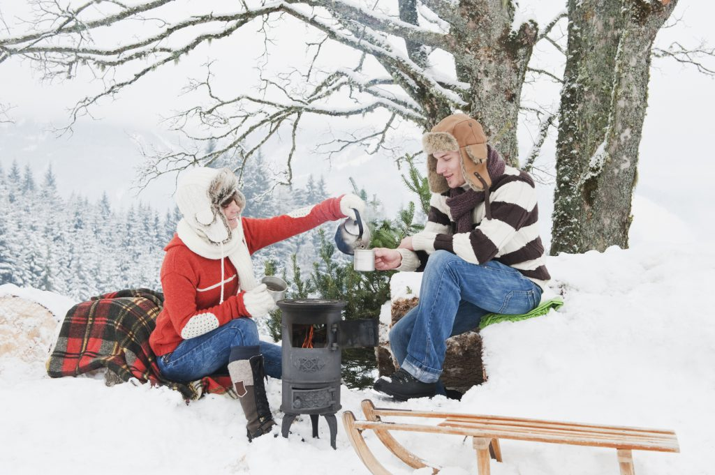 Austria,Salzburg Country,Flachau,Young man and woman making tea and sitting besides stove in winter