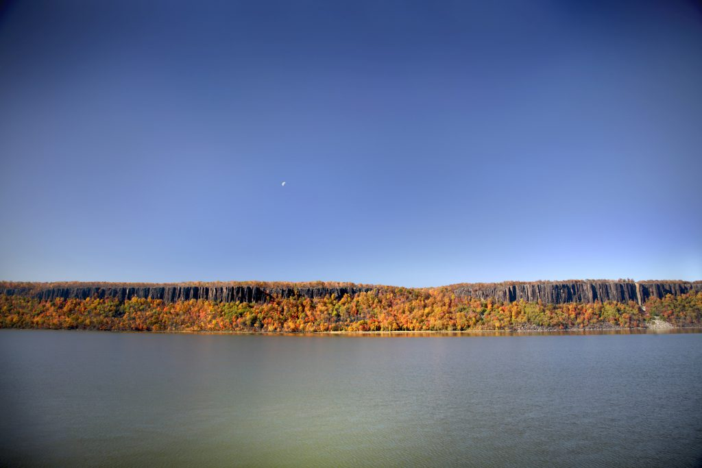 Sweeping view of the Palisades cliffs along the New York New/New Jersey border during Autumn. Early morning sunlight saturates the colors of the changing leaves just before the moon sets.